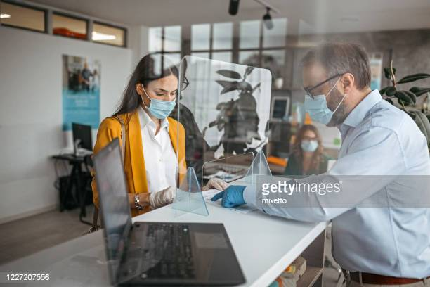 bank teller talking with customer at counter - illness prevention stock pictures, royalty-free photos & images