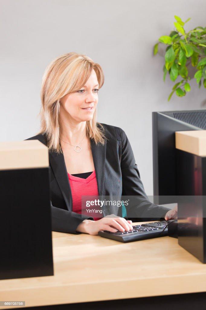 Bank Teller Working Behind Bank Counter At Retail Bank Stock Photo