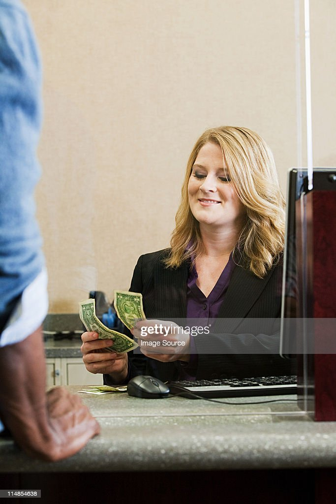 Bank teller working in bank : Stock Photo