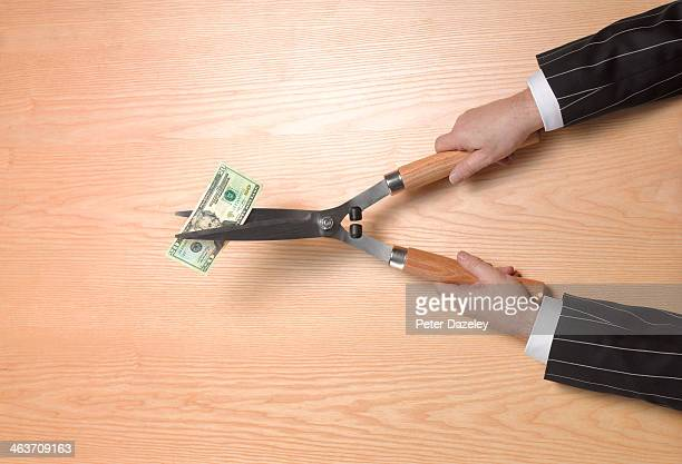 Banker cutting dollar note