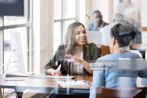 バンカーは、新しい顧客に銀行サービスを議論します - 銀行支店長 ストックフォトと画像