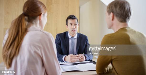 banker discussing with couple - ginger banks stock pictures, royalty-free photos & images