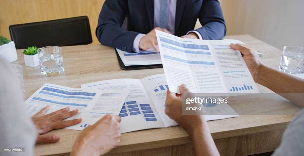 Banker discussing with couple : Stock Photo
