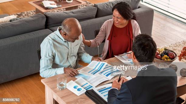 banker discussing with mature couple - flyer leaflet stock photos and pictures