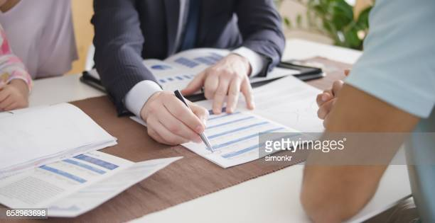 banker explaining to client - flyer leaflet stock photos and pictures