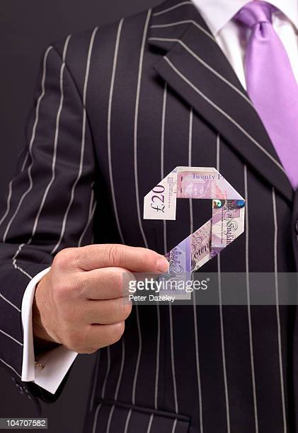 Banker holding 20 pound note question mark