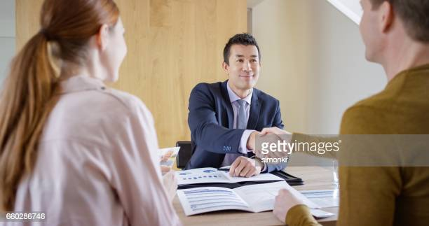 Banker shaking hands with man