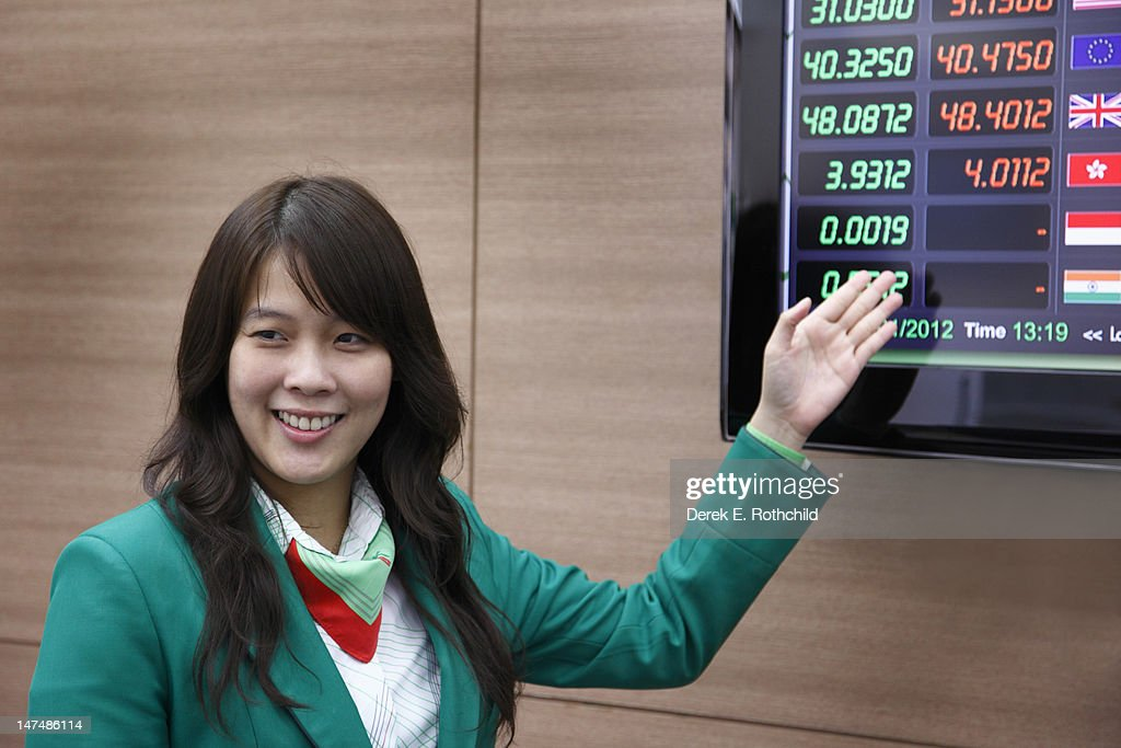 Banker showing exchange rates to customer : Stock Photo