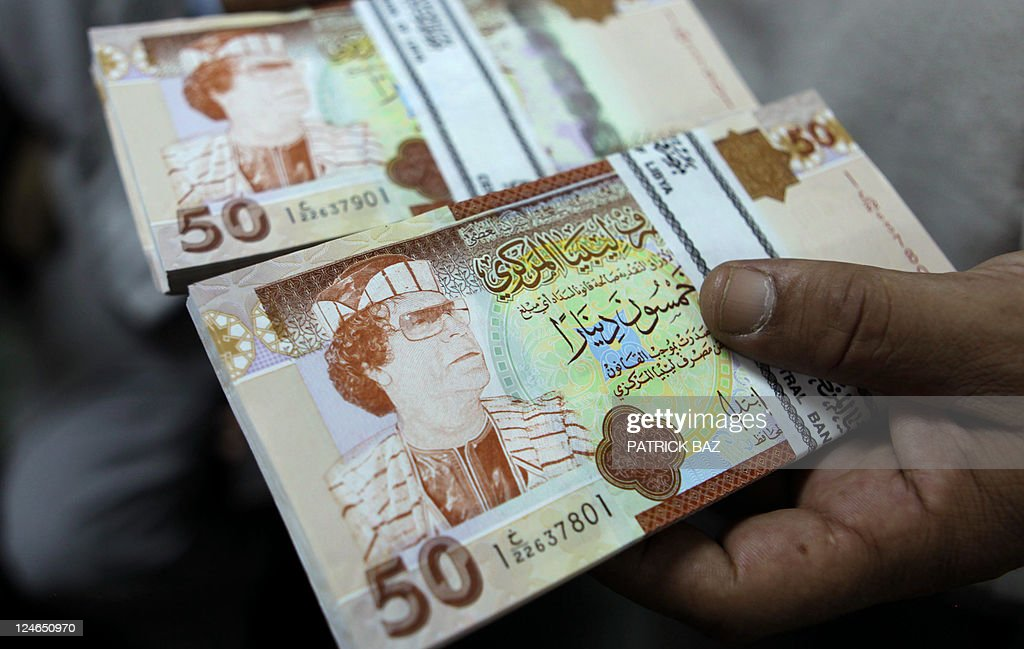 A banker shows 50 libyan dinar bank note pictures getty images a banker shows 50 libyan dinar bank notes bearing the portrait of ousted leader moamer kadhafi m4hsunfo