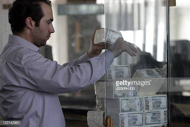 A banker stacks packed Syrian lira bills at the Central Bank in Damscus on August 25 2011 US sanctions have forced Syria to stop all transactions in...