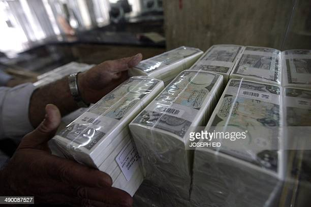 A banker stacks packed Syrian lira bills at the Central Bank in Damascus on August 25 2011 US sanctions have forced Syria to stop all transactions in...