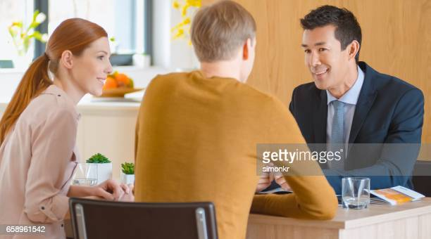 banker talking with couple - ginger banks stock pictures, royalty-free photos & images