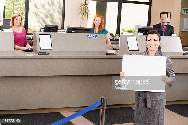 Banker with blank sign and happy tellers at the bank