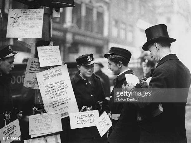 A banker writes a telegram to be given with the fee to the Post Office telegraph messengers who are stationed on the streets to provide quicker...