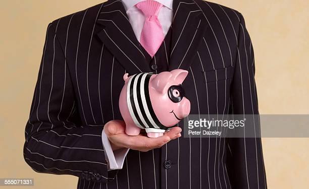 banker/financial advisor with burglar piggy bank - falsenews stock pictures, royalty-free photos & images