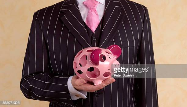 banker/financial advisor with holey piggy bank - failure stock pictures, royalty-free photos & images