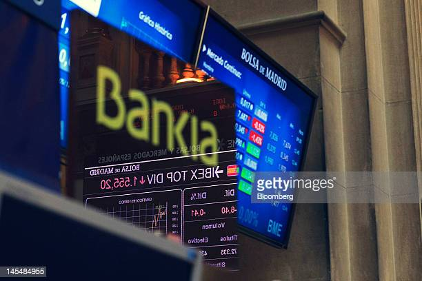 A Bankia SA logo is reflected on a screen near a display of stock prices at the Madrid stock exchange or Bolsas y Mercados in Madrid Spain on...