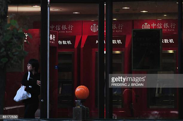 A banking customer leaves a 24hour automatic teller machine outlet branch of China CITIC Bank after finishing her transaction on October 8 2008 in...