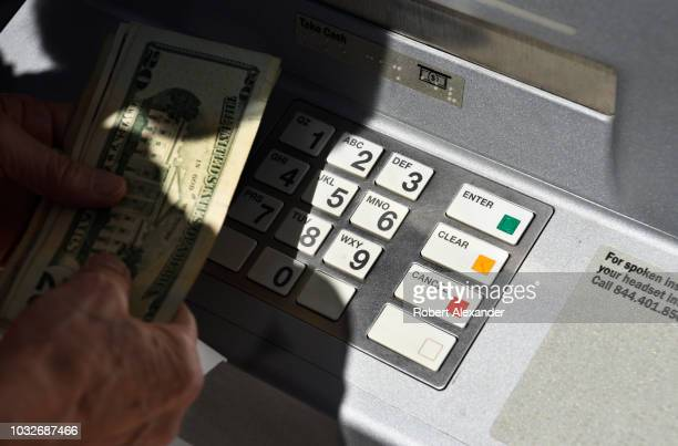 A banking customer withdraws money from a ATM machine in Santa Fe New Mexico