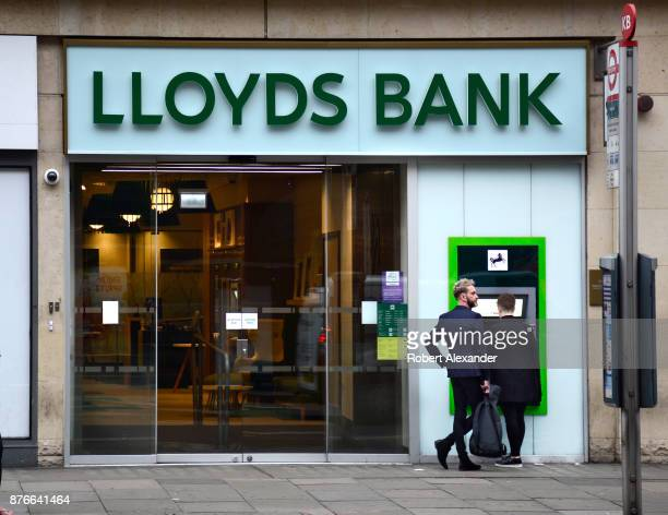 Banking customers use an ATM machine at a Lloyds Bank in London England Lloyds Bank is a British retail and commercial bank with branches across...