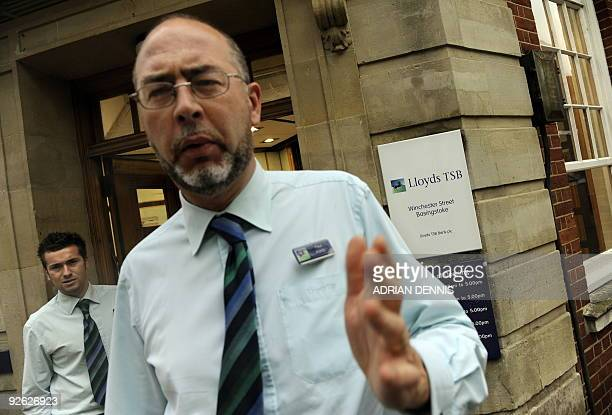 Banking staff ask a photographer not to take photographs of the doorway to a Lloyds TSB Bank in Basingstoke on November 3 2009 Britain is to force...