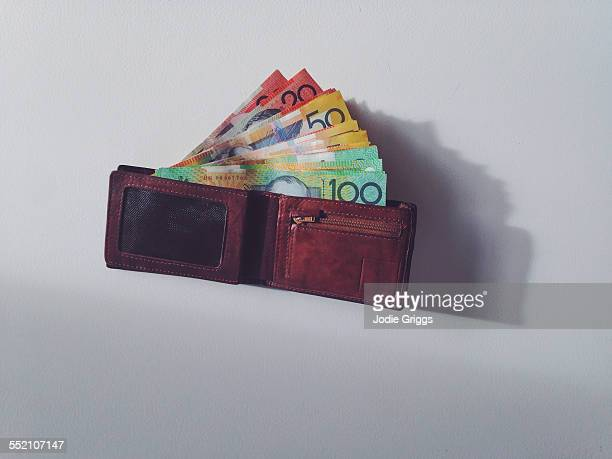 Banknotes coming out of a man's open wallet