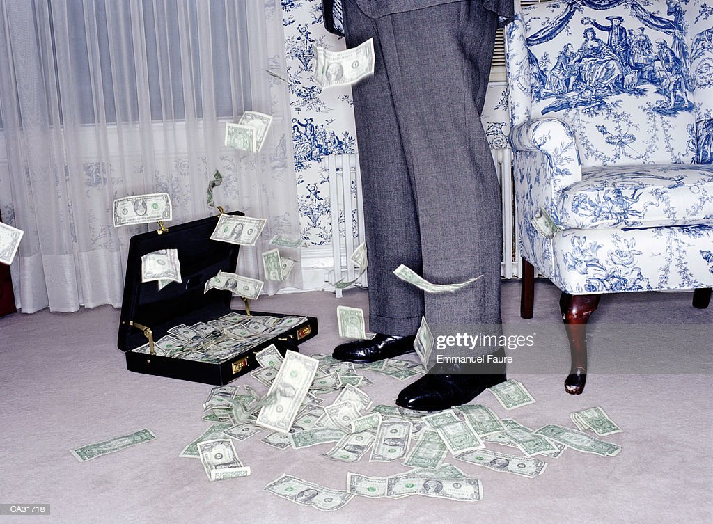 US banknotes falling around man in hotel room, low section : Bildbanksbilder