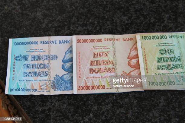 Banknotes from Zimbabwe worth up to one hundred trillion Zimbabwean dollars have been laid out on a table in Johannesburg, South Africa, 01 October...