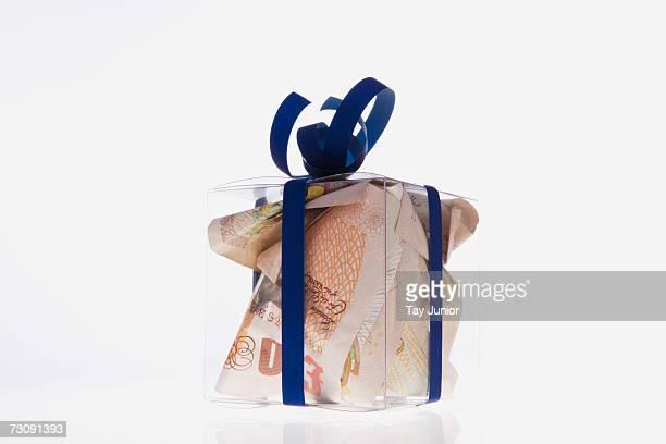 Banknotes inside clear gift box, studio shot
