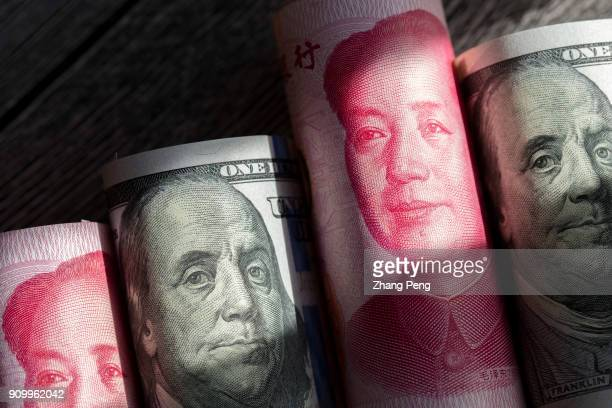 Banknotes of US Dollar and RMB are arranged for photography. Recently, the exchange rate of RMB vs US Dollar has continued to rise sharply. The...
