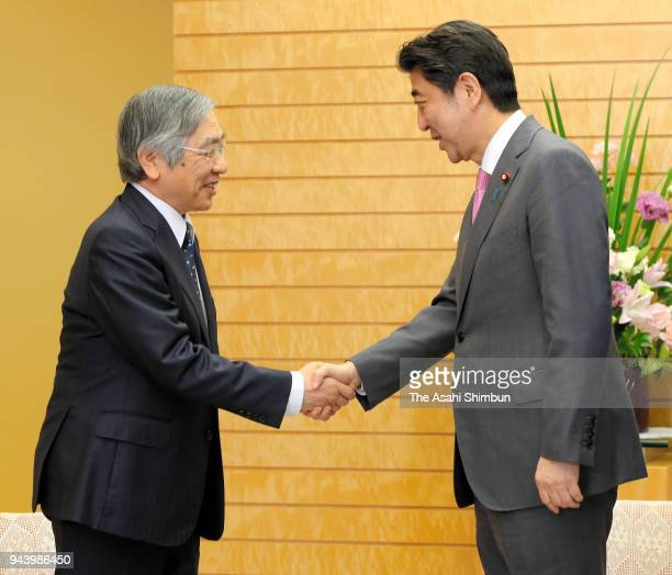 Banko of Japan Governor Haruhiko Kuroda shakes hands with Japanese Prime Minister Shinzo Abe during their meeting at the prime minister's official...