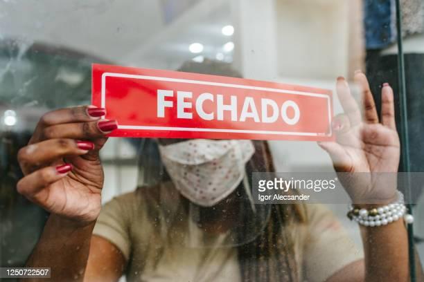 falência: mulher pendurada aviso fechado na loja - pandemia - fotografias e filmes do acervo