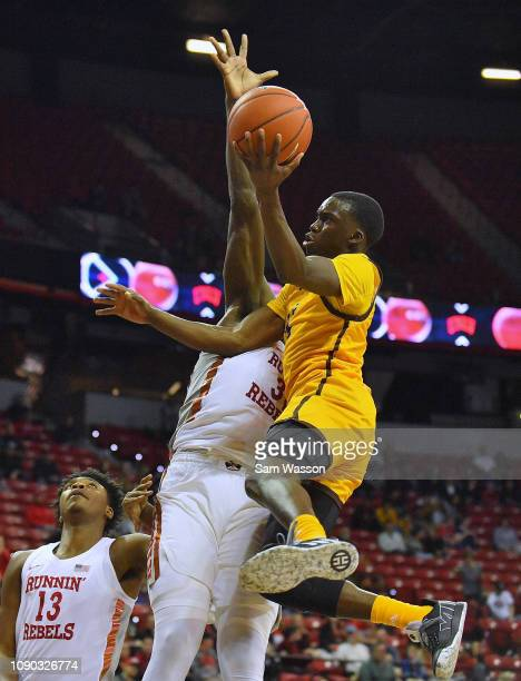 J Banks of the Wyoming Cowboys drives to the basket against Jonathan Tchamwa Tchatchoua of the UNLV Rebels during their game at the Thomas Mack...