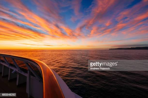 banks peninsula seen from a ship at sunrise - crociera foto e immagini stock