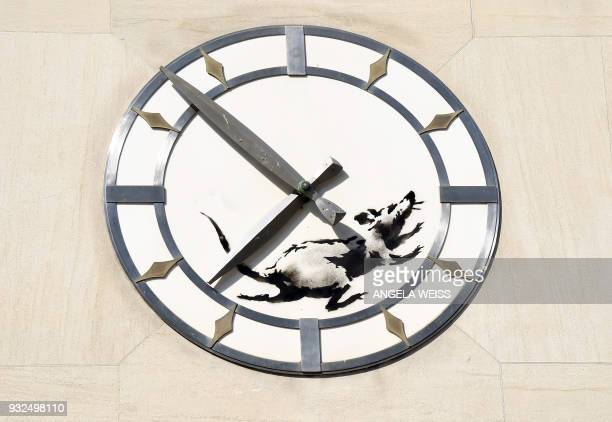 A Banksy painting of a rat running in a 14th Street clock face is seen on March 15 2018 on a building in New York City It is believed to be Banksys...