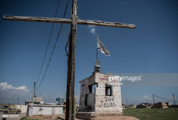 A banner bearing a crucifix is hung on the side of a guard box next to writing saying 'Love Jesus' at a checkpoint on a road leading into the nearly...
