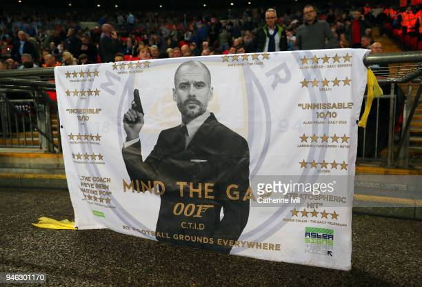 A banner bearing a picture of Pep Guardiola the head coach / manager of Manchester City dressed as James Bond saying mind the gap during the Premier...