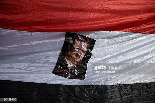 A banner bearing the image of Syrian President Bashar alAssad is carried by some of the 200 people demonstrating in support of alAssad and against a...
