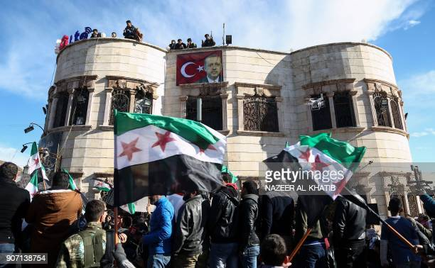 A banner bearing the Turkish flag and a picture of Turkish President Recep Tayyip Erdogan is seen hanging from a building while Syrians wave rebel...