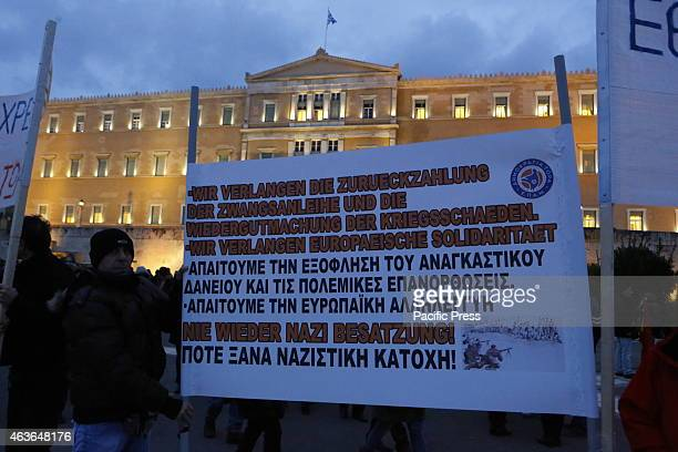 Banner calls in German and Greek for the repayment of the forced loan and reparation from World War II from Germany. Greeks protested a second day in...