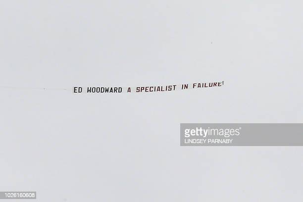 TOPSHOT A banner declaring 'Ed Woodward a specialist in failure' is flown over the ground before the English Premier League football match between...