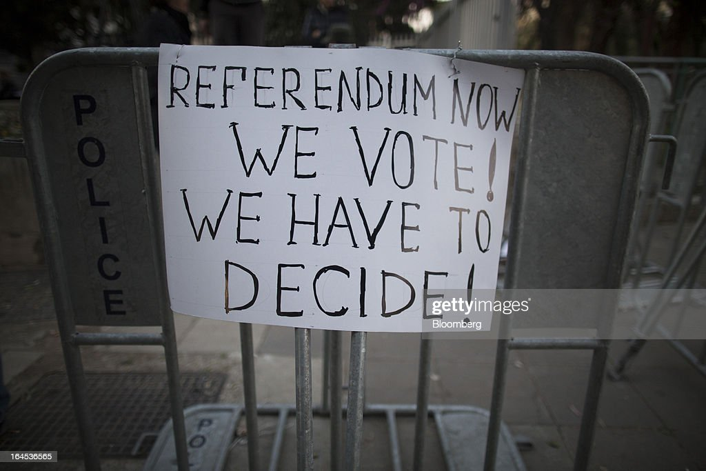 A banner demanding a referendum vote hangs on a police barrier during a demonstration outside the Cypriot parliament in Nicosia, Cyprus, on Sunday, March 24, 2013. Cyprus's fate hangs in the balance as euro-area finance ministers meet today to decide whether the tiny Mediterranean island has done enough for a bailout that will avert its financial collapse. Photographer: Simon Dawson/Bloomberg via Getty Images