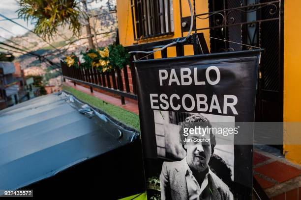 A banner depicting the drug lord Pablo Escobar is seen hung above a barber shop in the Pablo Escobar neighborhood in Medellín Colombia on December 06...