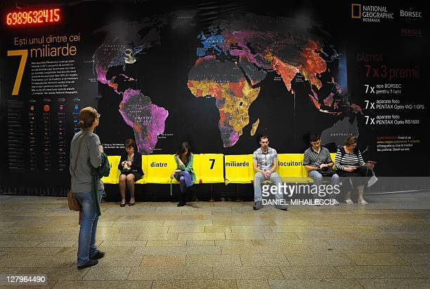 A banner displaying world map and population density by National Geographic Romania a counter showing the instant population of the Earth and benches...
