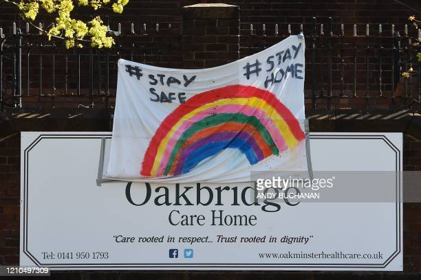 "Banner featuring a rainbow, being used as a symbol of hope during the COVID-19 pandemic, and the phrases ""Stay Safe"" ""Stay Home"", is pictured outside..."