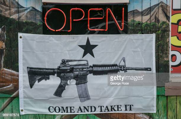Banner featuring an AR-15 automatic weapon hangs outside a Maggie Valley gift shop on May 11, 2018 near Cherokee, North Carolina. The Great Smoky...
