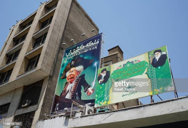 A banner in Ferdowsi Square depicts Queen Elizabeth as a sea pirate with a sword in her hand displayed next to another banner with images of...