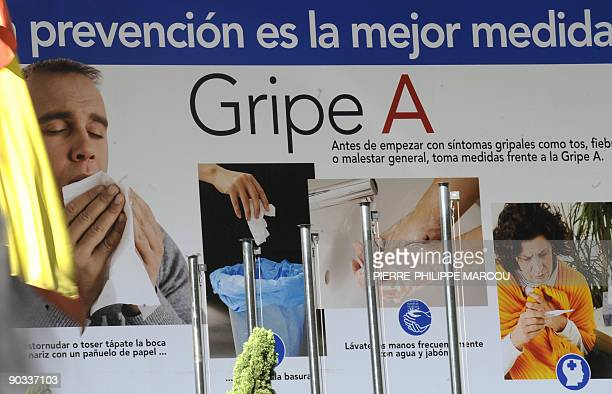 A banner informing of health guidelines to prevent the spread of swine flu is displayed at the entrance of the health ministry building in Madrid on...