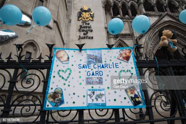 A banner is hung on a fence as supporters of of terminally ill baby Charlie Gard protest outside the High Court after the verdict was announced on...