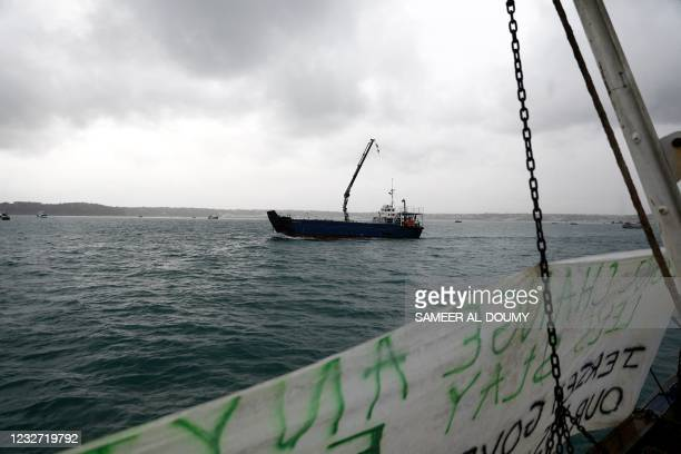 Banner is seen hanging off a fishing boat as other protest in front of the port of Saint Helier off the British island of Jersey on May 6, 2021. -...